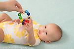 4 month old baby girl reaching up to grasp colorful wooden toy with moving rings