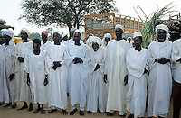 Sudan. West Darfur. Kerenek. According to the islamic tradition, a group of men pray in the afternoon. They are  dressed in white clothes and have a turban on the heads. Some men have sand on their foreheads because they kneel down and touch the ground with their heads while praying. © 2004 Didier Ruef