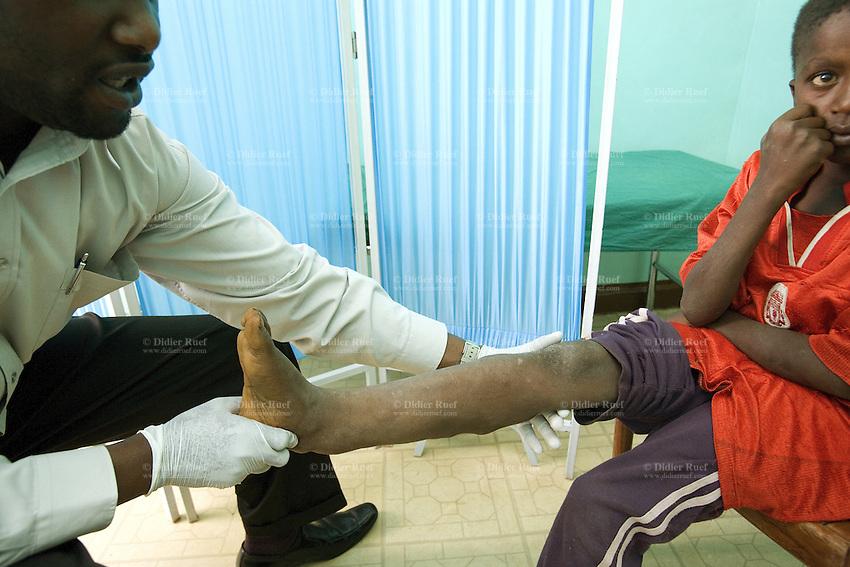 Kenya. Rift Valley province. Kasambara (20 km from Nakuru). Rhein-Valley hospital is ran by a swiss non-governmental organization (NGO). Medical consultation. The Kikuyu doctor John Wambugu, wearing white plastic gloves, examines the patient's leg of a young boy Steven Kamau Mwangi. The Kikuyus are Kenya's most populous ethnic group. © 2008 Didier Ruef