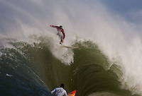"""Evan Slater (red) catches the wave over Darryl """"Flea"""" Virotsko (white) at the 2010 Mavericks Surf Contest in Half Moon Bay, California on February 13th, 2010."""