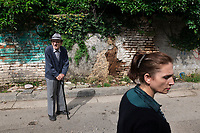 Albania. Tirana. Town center. An old man with a stick and woman walk on the road. Tirana is the capital and most populous city of the Republic of Albania. The city is also the capital of the surrounding county of Tirana, one of 12 constituent counties of the country. 20.5.2018 © 2018 Didier Ruef