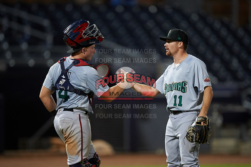 Surprise Saguaros catcher Jakson Reetz (4) and relief pitcher Josh Advocate (11) celebrate a victory after an Arizona Fall League game against the Peoria Javelinas on September 22, 2019 at Peoria Sports Complex in Peoria, Arizona. Surprise defeated Peoria 2-1. (Zachary Lucy/Four Seam Images)