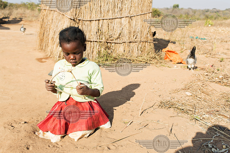 Catherine (3) plays in front of her home.