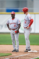 Greeneville Reds bench coach Reggie Williams (21) talks with Justin Bellinger (50) during the first game of a doubleheader against the Princeton Rays on July 25, 2018 at Hunnicutt Field in Princeton, West Virginia.  Princeton defeated Greeneville 6-4.  (Mike Janes/Four Seam Images)