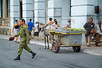 People walking past a horse and cart selling fruit on the streets of Pinar del Rio, Cuba.