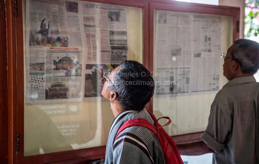 Yogyakarta, Java, Indonesia.  Reading Daily Newspaper, Posted in Display Cases for Public Viewing.