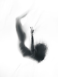 Surreal fine art photo of a woman silhouette falling down into white fog of a dream behind a veil Image © MaximImages, License at https://www.maximimages.com
