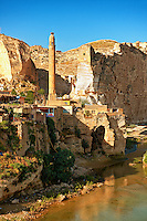 Remains of medieval Artukid Old Tigris Bridge – Built in 1116 by Artukid Fahrettin Karaaslan, the biggest in Anatolia at the time, with the old town Hasankeyf and its ruins on the cliffs abover the river Tigris. The minaret is of the El Rizk Mosque built 1409.  Turkey. 2