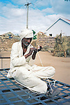 An elderly man makes a thin rope by winding several cords of string together.