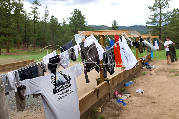 Photo story of Philmont Scout Ranch in Cimarron, New Mexico, taken during a Boy Scout Troop backpack trip in the summer of 2013. Photo is part of a comprehensive picture package which shows in-depth photography of a BSA Ventures crew on a trek. In this photo, a BSA Venture crew member  works to hang his washed clothes  on a clothesline provided at the Cimarroncito Camp in the backcountry at Philmont Scout Ranch.   <br /> <br /> The  Photo by travel photograph: PatrickschneiderPhoto.com