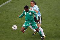 ofJonas Gutierrez (R) of Argentina and Yakubu Aiyegbeni (L) of Nigeria