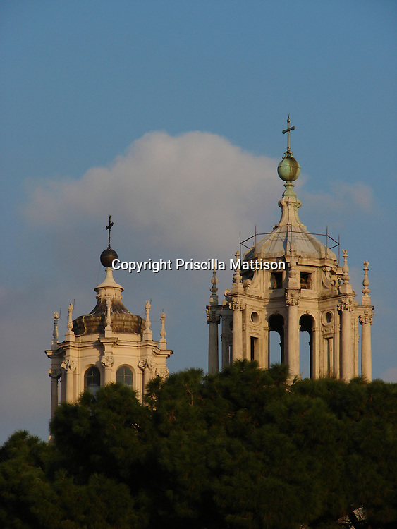 Rome, Italy - January 31, 2007:  The domes of Santa Maria di Loreto and Santissimo Nome di Maria al Foro Trainano rise above the treetops in the setting sun.