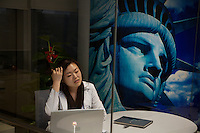 Wall Street English School in Beijing shows a captialist side of China.  Woman in office with Statue of Liberty poster is Sunny Wang.