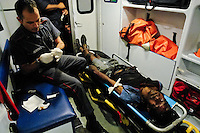 Venezuelan paramedics, members of the Caracas emergency medical service, try to save life of a homeless drug addict inside the ambulance car during the night of 25 June 2006, in Caracas, Venezuela.