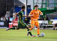 LAKE BUENA VISTA, FL - JULY 18: Zarek Valentin #4 of the Houston Dynamo is pressured by Jeremy Ebobisse #17 of the Portland Timbers during a game between Houston Dynamo and Portland Timbers at ESPN Wide World of Sports on July 18, 2020 in Lake Buena Vista, Florida.