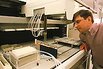 medical researcher watching machine process samples for PCR and DNA sequencing, genomics