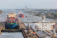 Panama Canal, Panama.  Two Ships Entering First Lock Heading South, Caribbean in far rear.  Third Ship Awaits its Turn.  Colon Port Cranes in far Background.