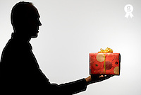 Silhouette of man holding gift against white background (Licence this image exclusively with Getty: http://www.gettyimages.com/detail/sb10068346at-001 )