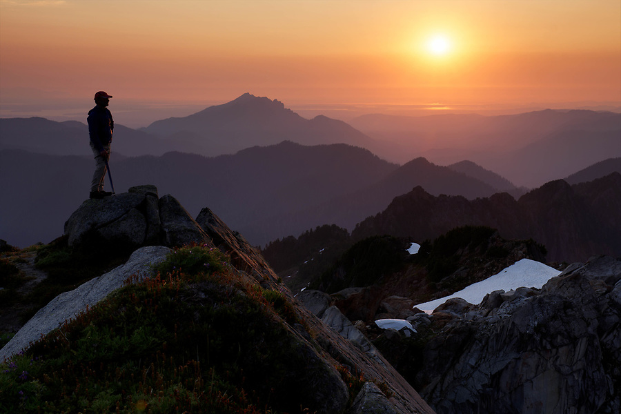 Climber on Vesper Peak at sunset with view of Central and North Cascade Mountains, Washington, USA