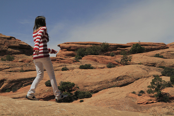 Young Hispanic woman on slickrock in Arches National Park, Utah, USA. .  John offers private photo tours in Arches National Park and throughout Utah and Colorado. Year-round.