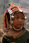 Akha girl in traditional headdress and western Tee shirt Northern Thailand South East  Asia. 1990s