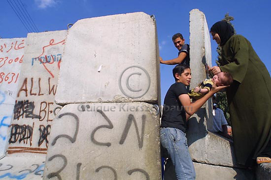 Miriam Fares passes her 4 months old son Wajd,  to an unidentified person as she is helped to climb on the concrete wall which separates the Abu Dis neighbourhood in east-Jerusalem from the West Bank, July 22, 2004. Photo by Quique Kierszenbaum