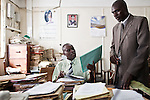 Detective Simiyu (R) delivers case files to  the registrar of Prosecutions, David Washike.
