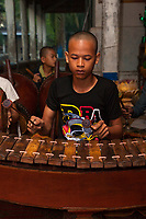 Cambodia, Angkor Wat.  Young Boy Playing Xylophone (Roneat).