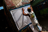 "A Colombian sign painter sticks a blank paper on the wall in the sign painting workshop in Cartagena, Colombia, 15 April 2018. Hidden in the dark, narrow alleys of Bazurto market, a group of dozen young men gathered around José Corredor (""Runner""), the master painter, produce every day hundreds of hand-painted posters. Although the vast majority of the production is designed for a cheap visual promotion of popular Champeta music parties, held every weekend around the city, Runner and his apprentices also create other graphic design artworks, based on brush lettering technique. Using simple brushes and bright paints, the artisanal workshop keeps the traditional sign painting art alive."