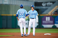 Omaha Storm Chasers Bobby Witt Jr. (7) is congratulated by Brandon Nelson (22) after hitting a double during a game against the Iowa Cubs on August 14, 2021 at Werner Park in Omaha, Nebraska. (Zachary Lucy/Four Seam Images)