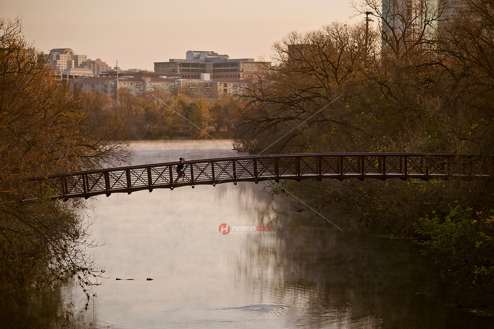Runners cross the pedestrian bridge during early morning as steam rises off Lake Austin
