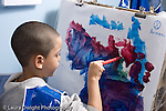 Educaton preschool 4-5 year olds art activtiy painting boy wearing smock at easel painting with brush horizontal