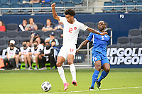 KANSASCITY, KS - JULY 11: Tajon Buchanan #12 of Canada with the ball,Karl Vitulin #5 of Martinique during a game between Canada and Martinique at Children's Mercy Park on July 11, 2021 in KansasCity, Kansas.