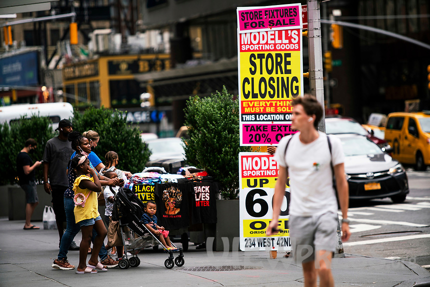 NEW YORK, NY - AUGUST 8: People walk near posters of a retail store closing in Times Square on August 8, 2020 in New York City. With more than four months NYC has closed some of their doors to combat the coronavirus, putting its vital tourism industry paralyzed with a moribund economy, where business and leaders are trying to revive an industry that brought in $45 billion annually and supported more than 300,000 jobs. (Photo by Eduardo MunozAlvarez/VIEWpress)