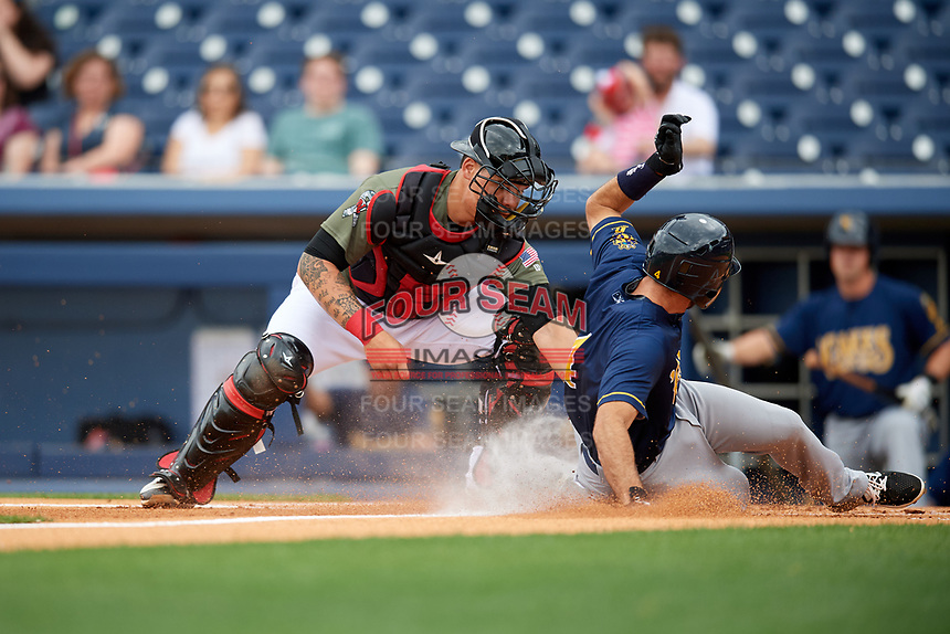 Nashville Sounds catcher Bruce Maxwell (36) puts a tag on Steve Lombardozzi (4) as he slides home during a game against the New Orleans Baby Cakes on April 30, 2017 at First Tennessee Park in Nashville, Tennessee.  The game was postponed due to inclement weather in the fourth inning.  (Mike Janes/Four Seam Images)