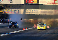 Nov 8, 2013; Pomona, CA, USA; NHRA funny car driver Jeff Arend (right) charges across the finish line along an engine blowing Josh Crawford during qualifying for the Auto Club Finals at Auto Club Raceway at Pomona. Mandatory Credit: Mark J. Rebilas-