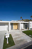 View of front facade of white mid-century home in prestine condition