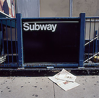 New York City Subway entrance with newspapers laying on sidewalk<br />