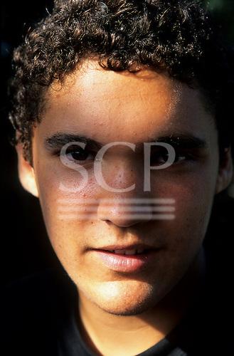 London, England. Teenage boy with dark brown eyes and short, very curly hair. Kit Cunningham.