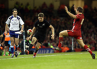Pictured: Beauden Barrett of New Zealand (L) kicks the ball forward and over Dan Biggar of Wales (R) to score yet another try for his team Saturday 22 November 2014<br />