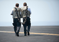 120403-N-DR144-054 INDIAN OCEAN (April 3, 2012) Sailors assigned to Carrier Airborne Early Warning Squadron (VAW) 125 carry a heavy chain used to secure aircraft for high power turns on the flight deck aboard the Nimitz-class aircraft carrier USS Carl Vinson (CVN 70). Carl Vinson and Carrier Air Wing (CVW) 17 are deployed to the U.S. 7th Fleet area of operations. (U.S. Navy photo by Mass Communication Specialist 2nd Class James R. Evans/Released)