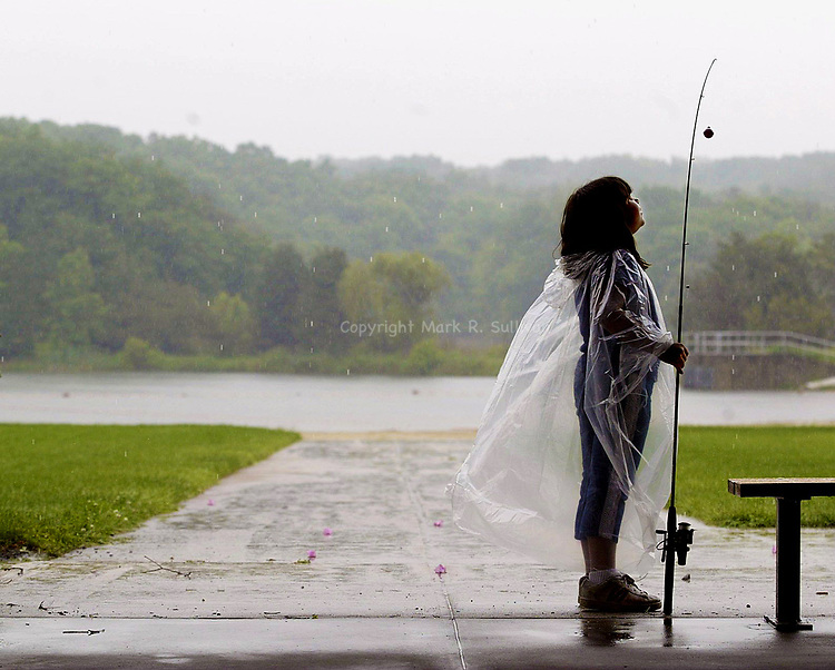 """(TAKE ME FISHING)--30370--On Sat June 7,2003-fish0607a--Natalie Ghigliotty, age 7 of South Amboy waits for the heavy rain to slow so she could go out and start fishing during the """"Take Me Fishing"""" day at Cheesequake State Park in Old Bridge Twp. The NJ Divison of Fish & Wildlife is sponsoring the event. (MARK R. SULLIVAN/HNT CHIEF PHOTOGRAPHER)"""