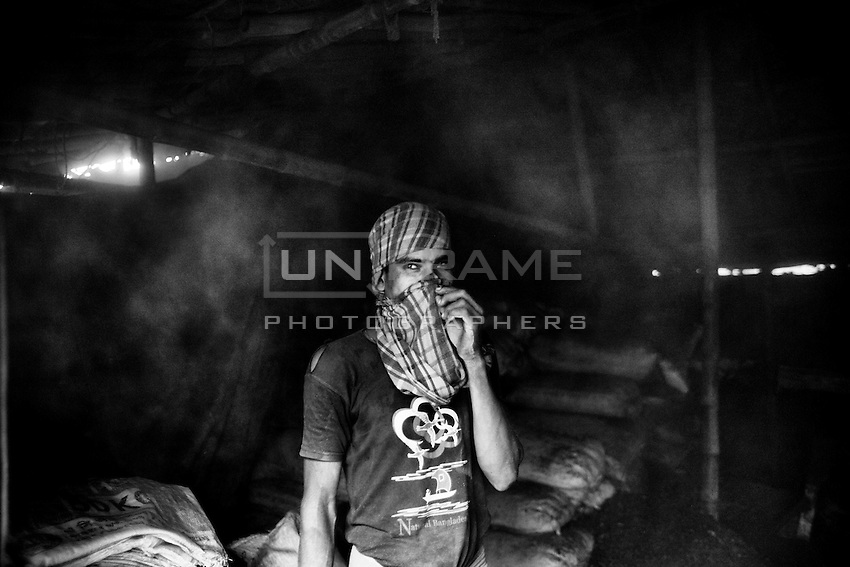 A Bangladeshi worker covers his face to protect himself from toxic dust in a wastage lather processing factory at Hazaribagh tannery area in Dhaka, Bangladesh.