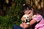 12 year old girl holding a yellow Labrador retriever puppy.  Fall.  Birchwood, WI.