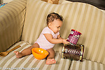 Infant development 9 month old baby girl sitting on couch hitting metal can against large metal coffee can