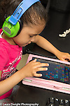 Education preschool 3-4 year olds girl wearing headphones and using tablet computer to play game