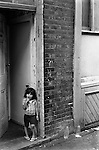 Child outside her front door. East end London, Whitechapel 1970s England...My ref 6/1059/, 1975,