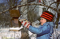BF01-001z  Bird feeder - girl putting seeds in feeder during winter