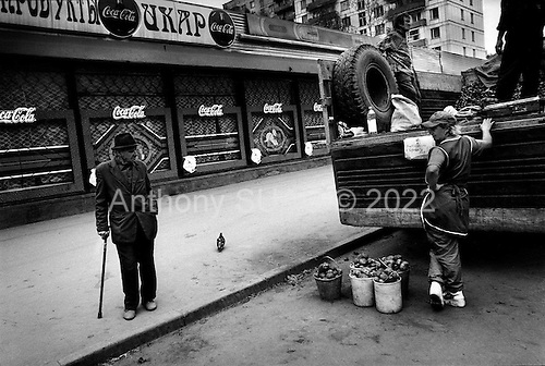Moscow, Russia  .1998. A pensioner eyes potatoes being sold off the back of a truck for very little money. Unfortunately he cannot purchase any and moves on. Most people were stocking up on these goods for the approaching winter..
