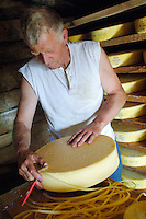Trimming the edge of the rind forming on a Alp cheese...Cowherd and cheesemaker spends 100 days in the summer, high up in the mountains, tending cows and pigs and making cheese at Balisalp and Käserstatt near Meiringen, Switzerland.